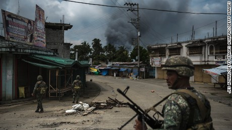 Soldiers patrol a street as smoke billows from a fire caused by heavy gunfights and aerial strikes on June 6, 2017 in Marawi.