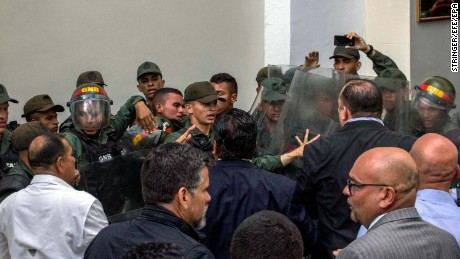 Members of the National Guard clash with deputies of the National Assembly in the courtyard of the Parliament in Caracas on Tuesday.