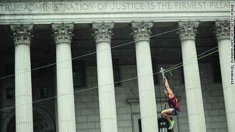 A woman rides a zip line in front of a Manhattan court house during the Summer Streets event in New York, August 3, 2013. Summer Streets is an annual event that closes miles of New York roadway from uptown to downtown to car traffic, so pedestrians can walk, bike, run, do yoga or take part in activities such as ride a zip line, climb a climbing wall or participate in fitness or dance programs along the way.  AFP PHOTO/Emmanuel Dunand        (Photo credit should read EMMANUEL DUNAND/AFP/Getty Images)