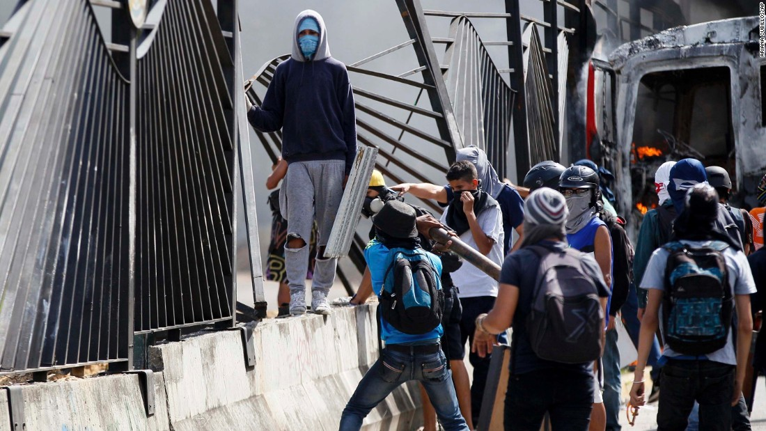 "Protesters tear down a fence at the La Carlota airbase outside Caracas on Friday, June 23. A soldier <a href=""http://www.cnn.com/2017/06/23/americas/venezuela-protest-shooting-video/index.html"">shot a demonstrator through the fence </a>at the base on the previous day, killing him."