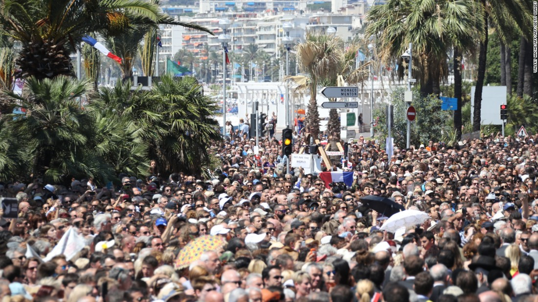 A French flag was raised as people gathered to observe a minute's silence at the Jardin Albert 1er on the Promenade des Anglais seafront in Nice in tribute to the victims of the deadly Nice attack on Bastille Day.