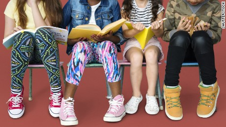 Diverse group of kids sitting in a row reading books.