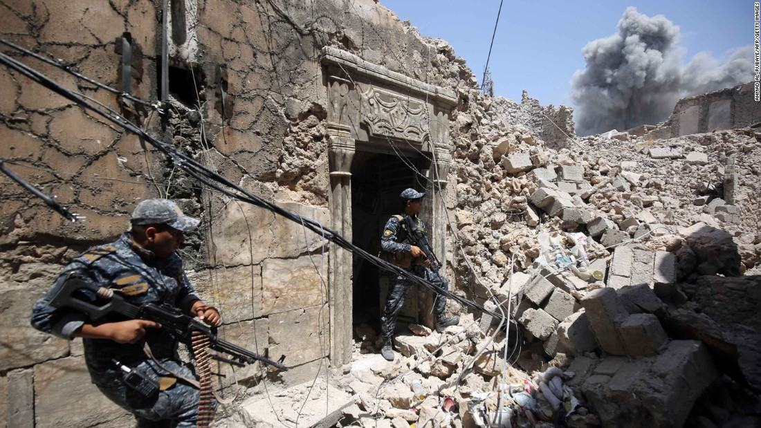 Members of the Iraqi Federal Police hold a position as US-led coalition forces advance through the Old City on Wednesday, June 28.