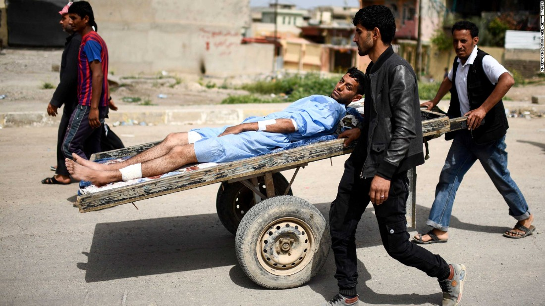 A wounded man is transported in western Mosul on Friday, April 21.