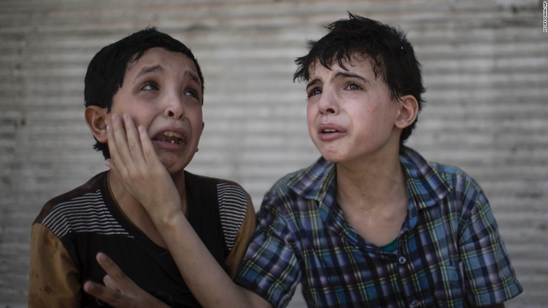 Two boys comfort each other after their home collapsed during fighting between Iraqi forces and militants in Mosul on Saturday, June 24. The boys, who are cousins, said some of their relatives were still under the rubble.