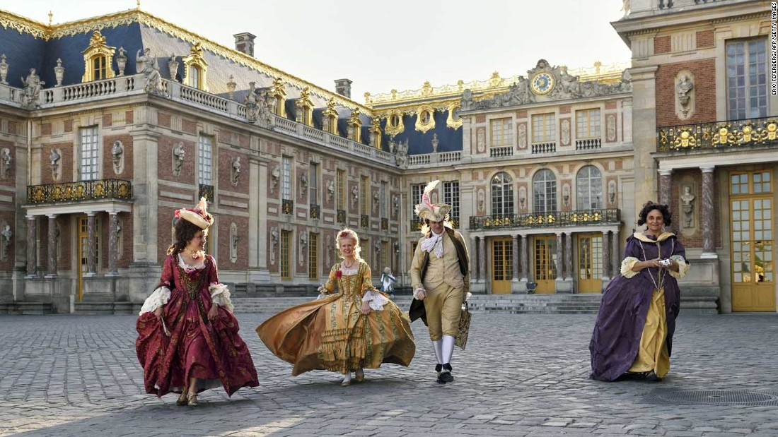 People dressed in period costumes walk across the courtyard at the Palace of Versailles.