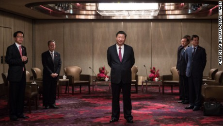 Xi Jinping (C) waits to meet with Hong Kong's chief executive Leung Chun-ying at a hotel in Hong Kong on June 29.