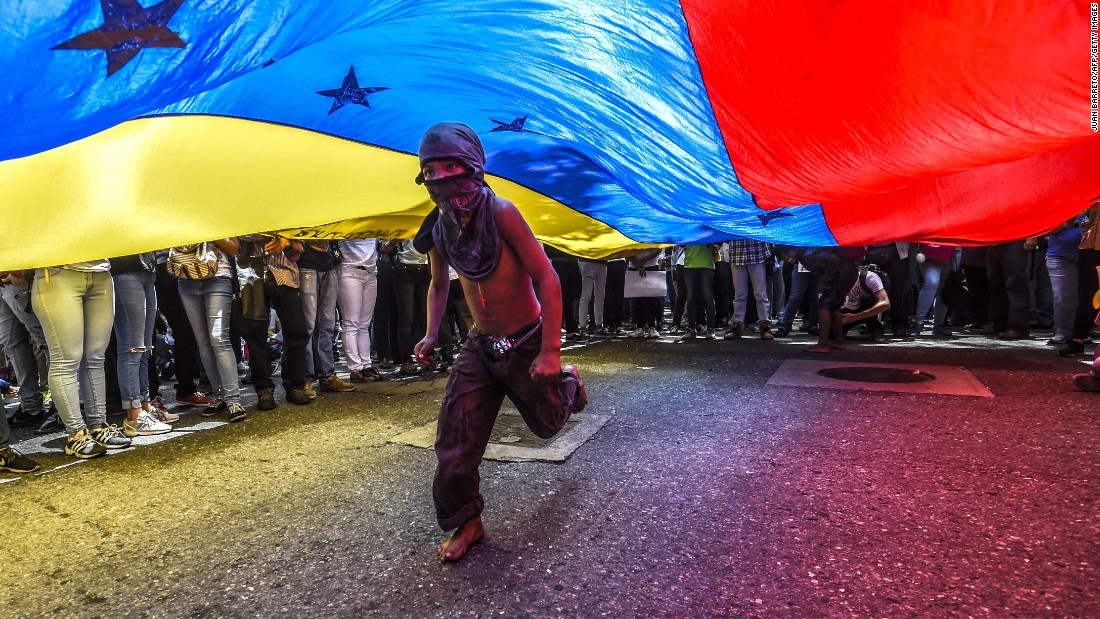 "A boy runs under a Venezuelan flag in Caracas on June 27, during a protest of journalists and media workers against recent attacks on the press. The country has been in the throws of economic and political turmoil, including attacks on the Supreme Court by a <a href=""http://www.cnn.com/2017/06/29/americas/venezuela-unrest/index.html"" target=""_blank"">police helicopter</a>."