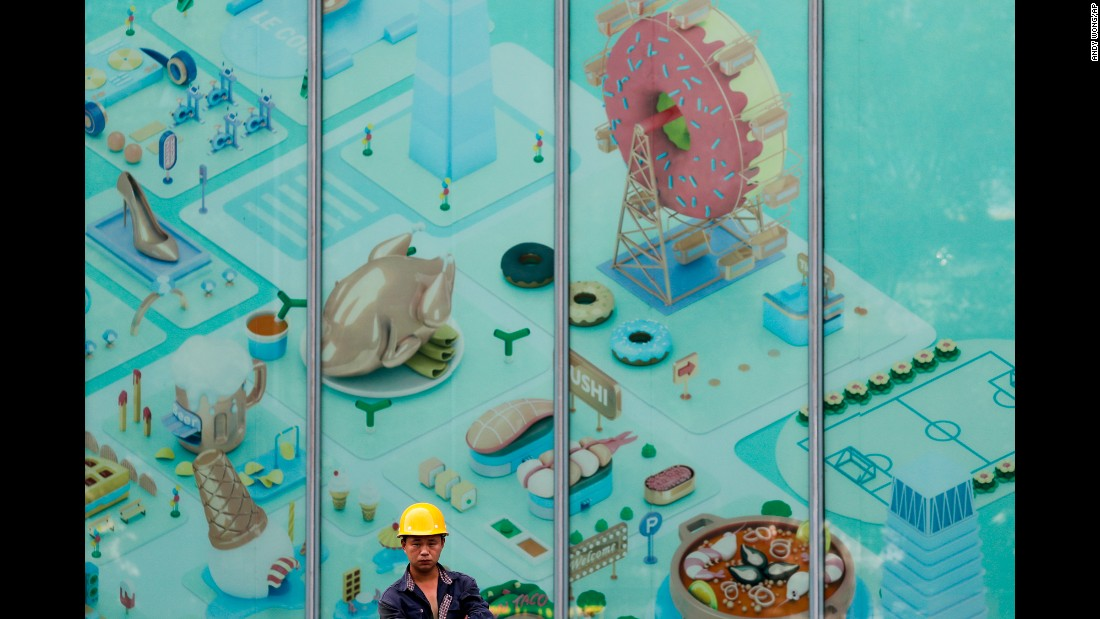 A Chinese worker stands near window panels displaying a map of a newly opened shopping mall at the Central Business District in Beijing on Tuesday, June 27.