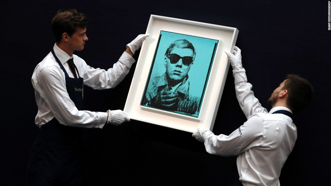 Sotheby's employees hang a self-portrait by Andy Warhol during a press viewing at its gallery in London on Friday, June 23. The painting was auctioned in the Contemporary Art Evening sale on June 28 and sold for $7.7 million US dollars.