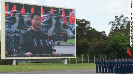 Chinese President Xi Jinping (on screen) reviews troops from a car during a military parade in Hong Kong on June 30, 2017.