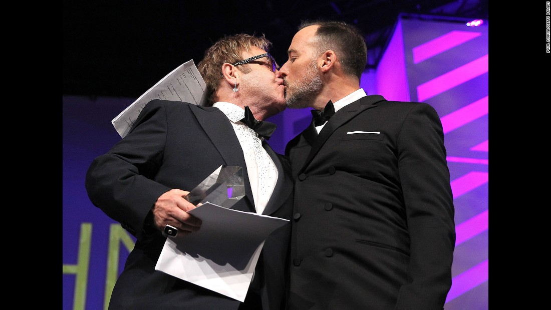 John and Furnish kiss at the Human Rights Campaign's National Dinner in 2014. They married in December of that year.