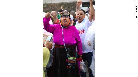 A woman in traditional Aegean clothes participates in the Justice March.