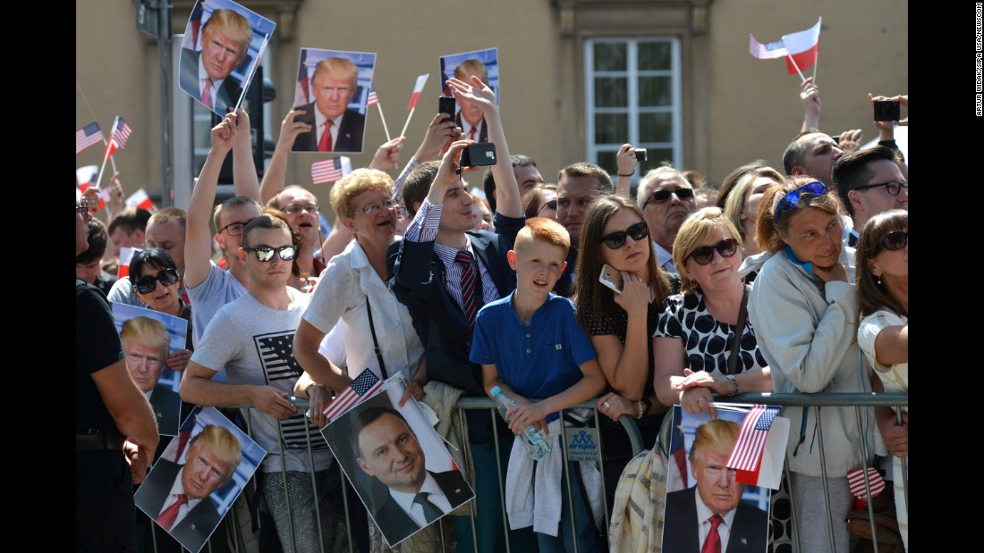 People hold up pictures of Trump during his speech in Warsaw.