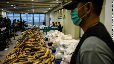 A customs officer stands guard next to seized elephant ivory tusks during a news conference at the Kwai Chung Customhouse Cargo Examination Compound in Hong Kong on Thursday.