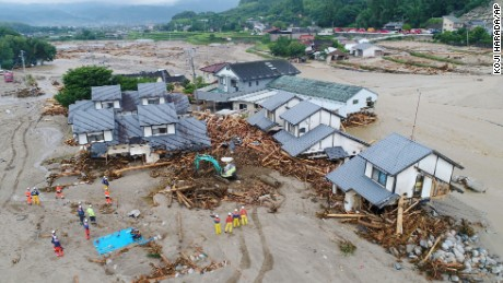 Firefighters inspect the collapsed houses in the mud following the flooding caused by heavy rain in Asakura, Fukuoka prefecture, southwestern Japan, Saturday, July 8, 2017.