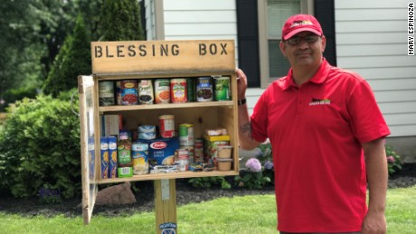 "Roman Espinoza stands beside his ""Blessing Box,"" which allows residents of Watertown, New York, to donate and take food as needed."