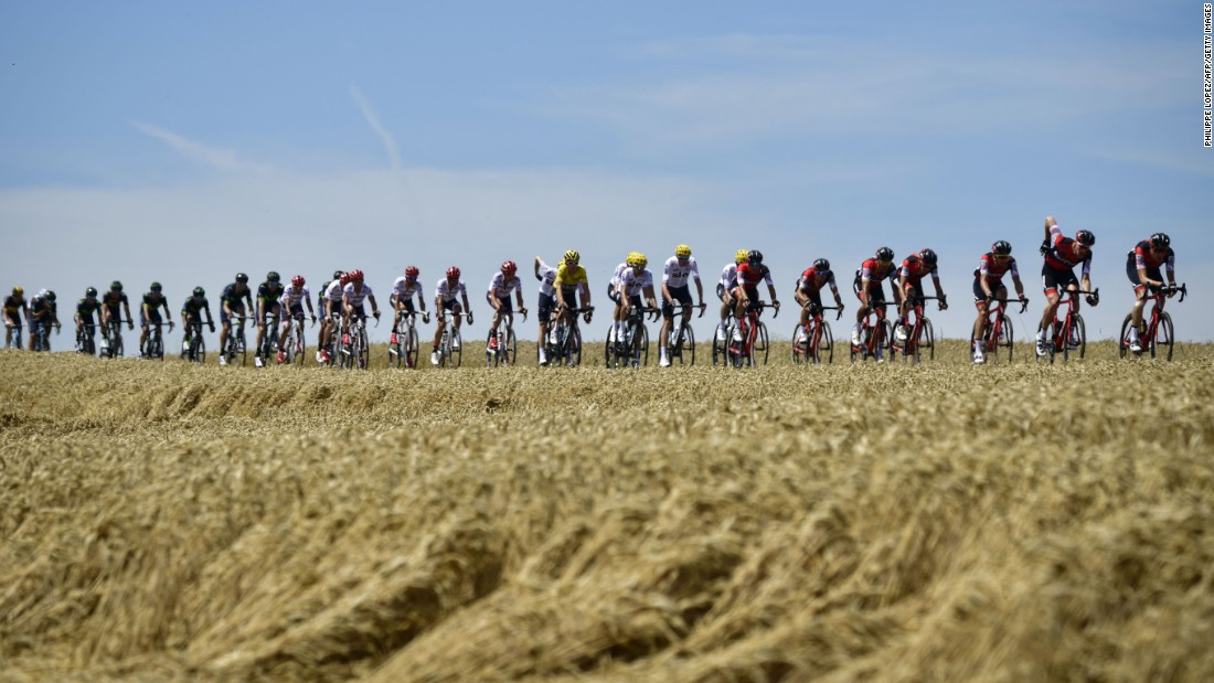 The pack, including Thomas (C) wearing the overall leader's yellow jersey, rides during the 160.5 km fifth stage between Vittel and La Planche des Belles Filles.