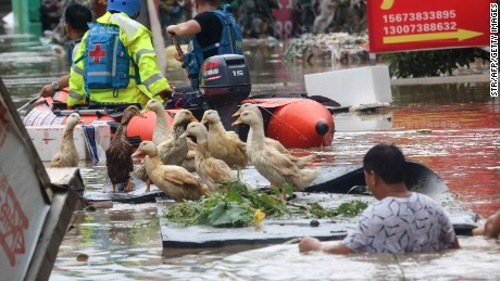 Rescue workers helping people on a flooded street in Loudi, Hunan province, in July 2017.