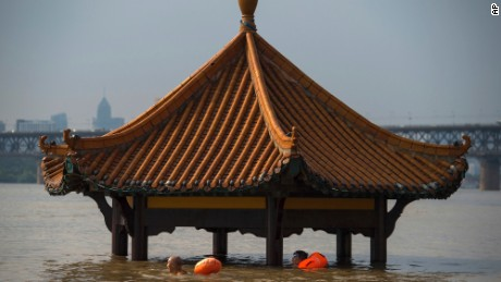 People swim past the top of a pagoda at a flooded riverside park in Wuhan in central China's Hubei Province on Monday, July 3, 2017. Dozens have been killed and more are missing as heavy rains pummeled southern China, flooding towns, cutting off power and halting traffic, China's Ministry of Civil Affairs said Tuesday. (Chinatopix Via AP)