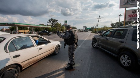 State Police elite group personnel patrol a street during a security operation in Jamay, Jalisco State Mexico, on September 30, 2016. Three more corpses were found on the banks of the Lerma River, near Lake Chapala  raising the count to 13 bodies. / AFP / HECTOR GUERRERO        (Photo credit should read HECTOR GUERRERO/AFP/Getty Images)