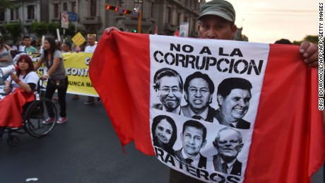 A man carries a flag with the faces of former Peruvian presidents Alberto Fujimori, Alejandro Toledo and Alan Garcia, former first lady Nadine Heredia and her husband, former president Ollanta Humala, and current President Pedro Pablo Kuczynski, while thousands march against corruption through the streets of downtown Lima on February 16, 2017. Accusations that Brazilian construction giant Odebrecht paid millions in bribes to secure contracts for public works across Latin America have now affected former Peruvian President Alejandro Toledo (2001-2006), presumably in the United States, who has been sentenced in absentia to 18 months of pre-trial detention. / AFP / CRIS BOURONCLE        (Photo credit should read CRIS BOURONCLE/AFP/Getty Images)