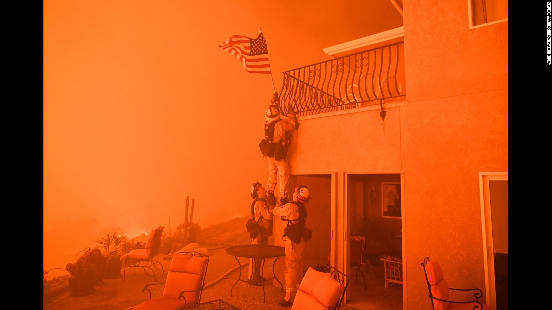 "Firefighters <a href=""http://www.cnn.com/2017/07/10/us/california-wildfires-firefighter-photo-trnd/index.html"" target=""_blank"">remove an American flag</a> as a wildfire closes in on a home in Oroville, California, on Saturday, July 8. Raging wildfires have forced thousands of people to evacuate their homes across the Western United States."