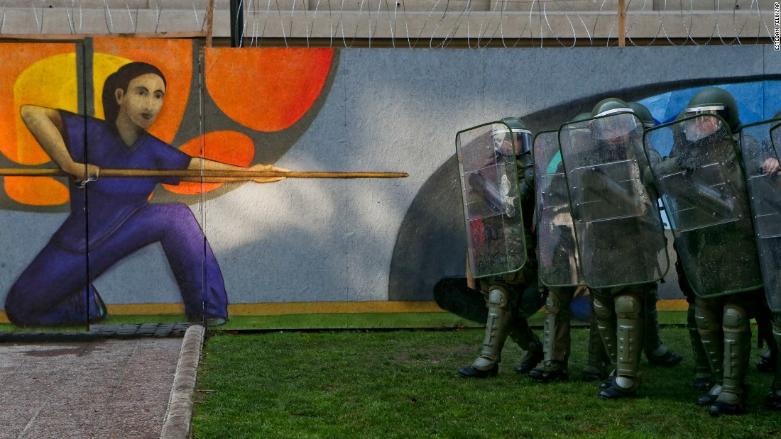Police officers in riot gear walk next to an art museum as they confront protesters in Santiago, Chile, on Monday, July 10. Gay rights activists were clashing with people who were demonstrating against a gender identity bill in Chile's Congress.