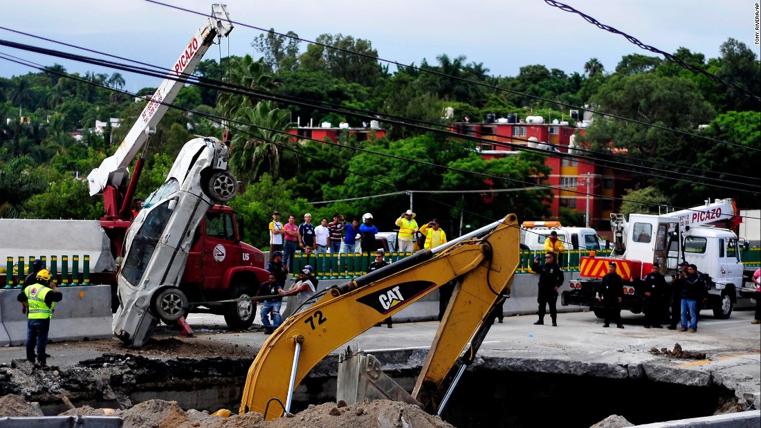 A crane lifts a vehicle out of a sinkhole that opened up on a highway in Cuernavaca, Mexico, on Wednesday, July 12. A man and his son were killed.
