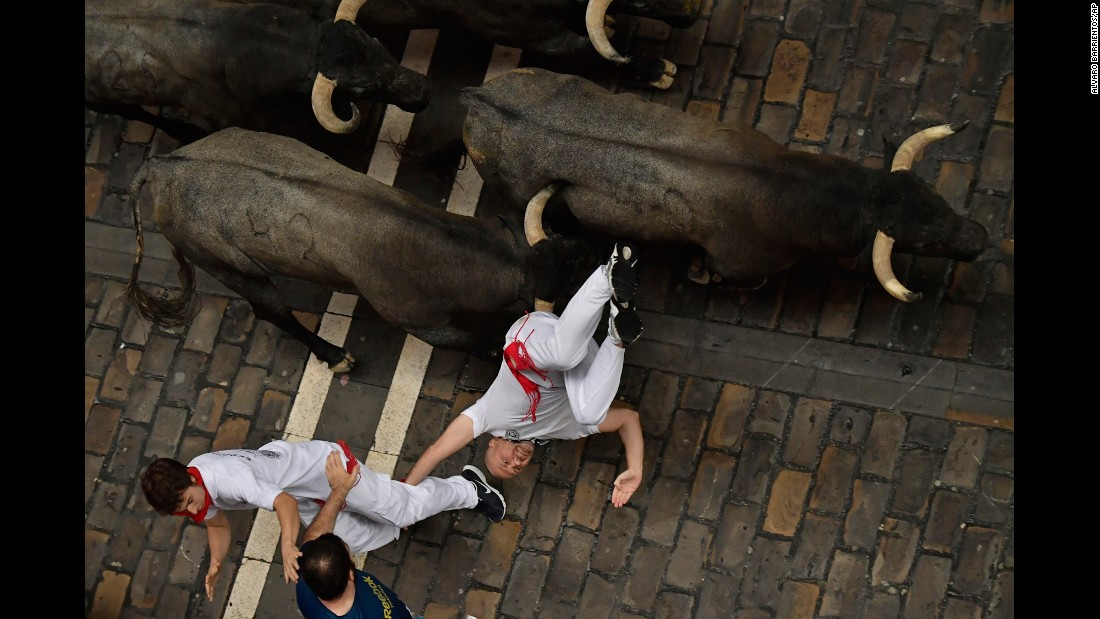 "A reveler falls during the annual ""running of the bulls"" in Pamplona, Spain, on Saturday, July 8."