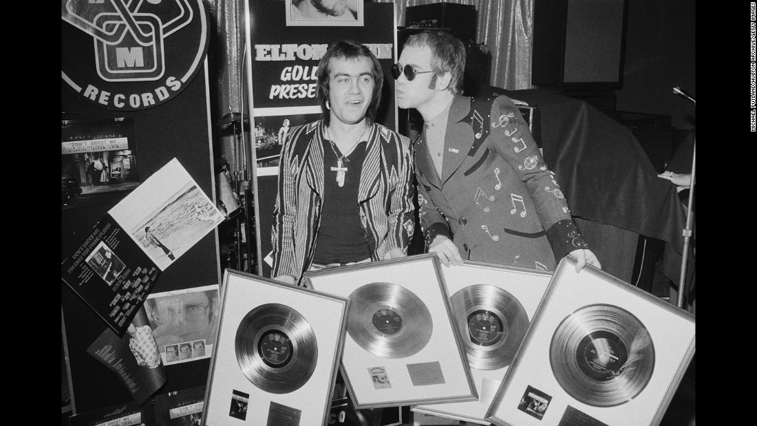 John and his songwriting collaborator, Bernie Taupin, hold gold records in 1973. Taupin has written the lyrics for many of John's songs over his career, and the two have worked together for decades.