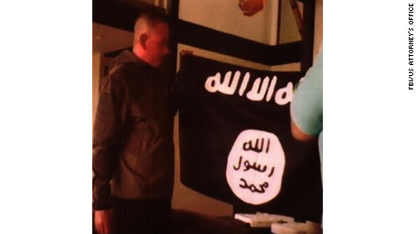 The soldier holds an ISIS flag in another photo that prosecutors presented.