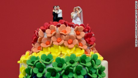 TOPSHOT - A wedding cake in rainbow colors and decorated with figurines of two women and two men is pictured in Berlin on June 30, 2017. The German parliament legalised same-sex marriage, days after Chancellor Angela Merkel said she would allow her conservative lawmakers to follow their conscience in the vote. / AFP PHOTO / Tobias SCHWARZ        (Photo credit should read TOBIAS SCHWARZ/AFP/Getty Images)