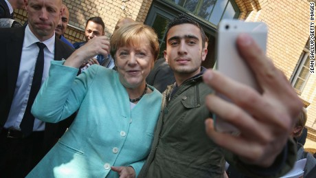 Merkel poses for a selfie with a Syrian refugee at a shelter in Berlin in September 2015.