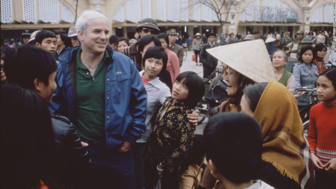 "McCain talks with people in Hanoi, Vietnam, during the filming of the CBS special ""Honor, Duty and a War Called Vietnam"" in 1985."