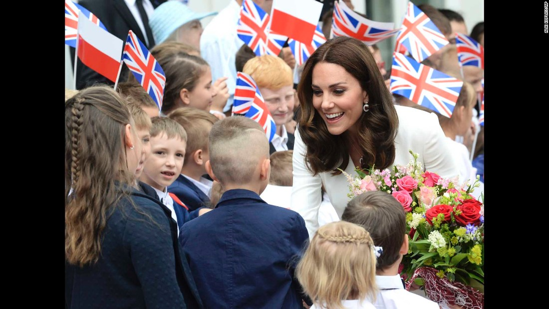 Children welcome Kate in front of the presidential palace in Warsaw upon the royal family's arrival in Poland.