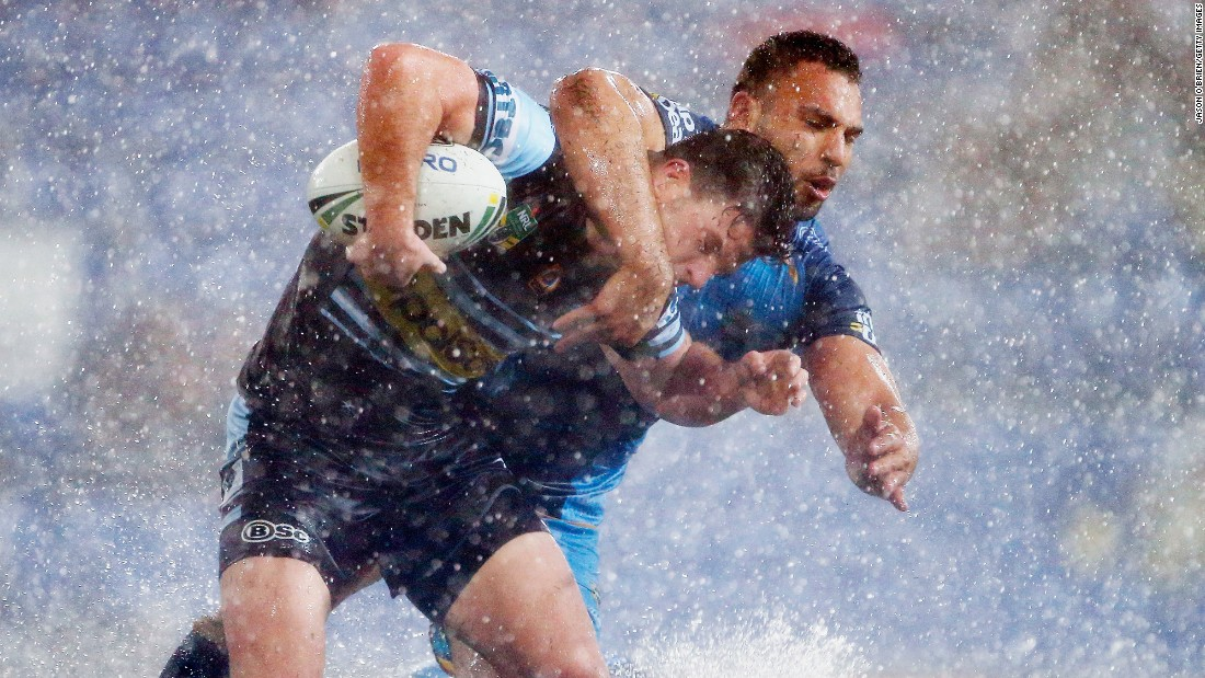 Chad Townsend of the Sharks, left, is tackled by Ryan James of the Titans during an NRL match between the Gold Coast Titans and the Cronulla Sharks on Saturday, July 15, in Gold Coast, Australia.