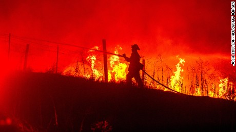 A firefighter sprays down flames as the Detwiler fire rages on near Mariposa, California on Tuesday, July 18.