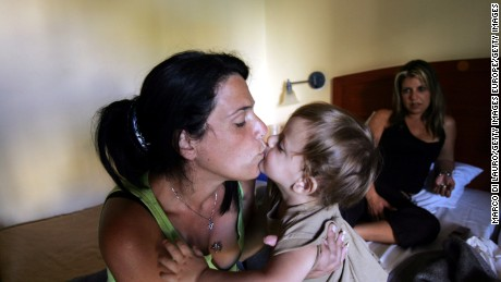 YEHUD, ISRAEL - AUGUST 24:  Jewish settler Mali Alush, 33 kisses the baby of Smadar Ben Hyon (background) 36, as she sits on a bed on August 24, 2005 in the Avia hotel in Yehud, Israel. Hyon, who is pregnant and already has five children, and her husband Shimon had been living in the Nisanit Settlement for three years, but because they did not own the house, they are not entitled for full compensation from the Israeli government. They are now temporarily living in the hotel assigned to them from the government, but they will have to find another place by August 28. After the disengagement she was moved to the Avia hotel where 33 families live, about 100 of whom are from the Nisanit Settlement, as they wait for their house to be finished or for the government to find a solution for them.  (Photo by Marco Di Lauro/Getty Images)
