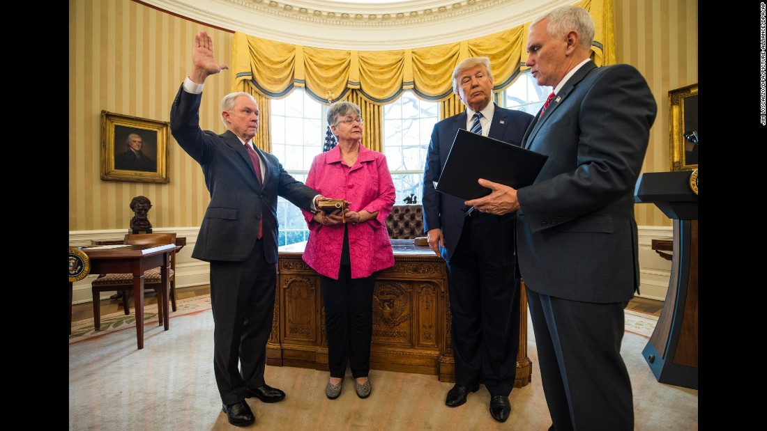 Vice President Mike Pence swears in Sessions as attorney general while Sessions' wife and President Trump look on in the Oval Office on February 9, 2017. Sessions was approved after a contentious battle along party lines.