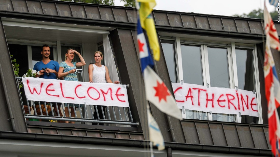 Residents stand on a balcony decorated with a banner welcoming the Duchess of Cambridge to Heidelberg, Germany.