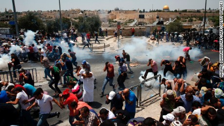Palestinian worshippers run for cover from teargas, fired by Israeli forces, following prayers outside Jerusalem's Old City in front of the Al-Aqsa mosque compound after Israeli police barred men under 50 from entering the Old City for Friday Muslim prayers as tensions rose and protests erupted over new security measures at the highly sensitive holy site on July 21, 2017. The ban came after Israeli ministers decided not to order the removal of metal detectors erected at entrances to the Haram al-Sharif mosque compound, known to Jews as the Temple Mount, following an attack nearby a week ago that killed two policemen. / AFP PHOTO / AHMAD GHARABLI        (Photo credit should read AHMAD GHARABLI/AFP/Getty Images)