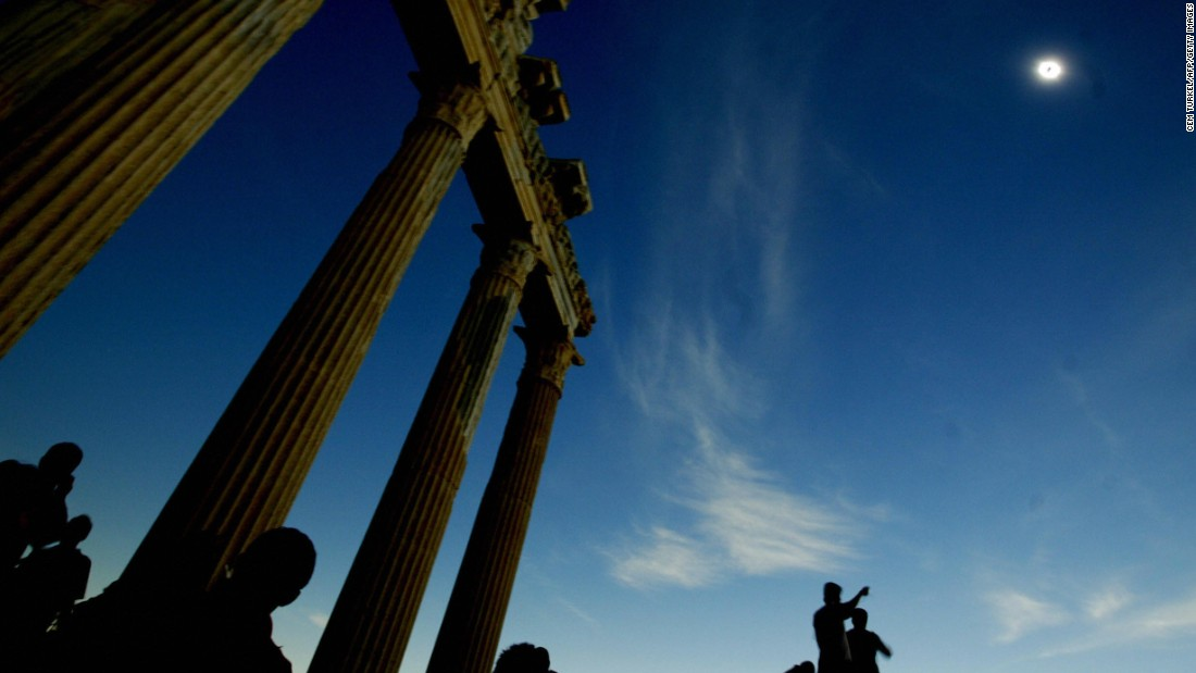 Tourists watch the full solar eclipse in the second century Greek Temple of Apollo in Side, Antalya, on the southern coast of Turkey in March 2006.