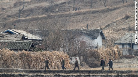 North Korean men walk amid a dry and barren landscape on the banks of the Yalu River in November 2010.