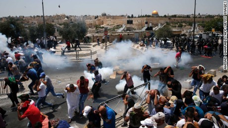 Palestinians run for cover from tear gas fired by Israeli forces following prayers outside Jerusalem's Old City on Friday.