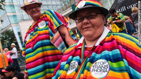 "Dressed in vibrant, multi-colored outfits, some participants worn ""Stop transphobia"" stickers as well."