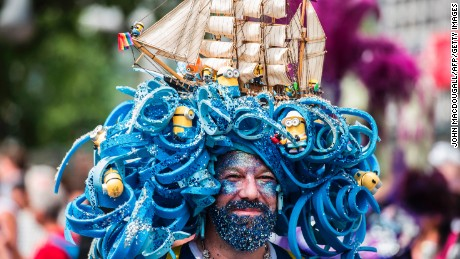 A man wears an intricate headpiece featuring a model ship and minions.