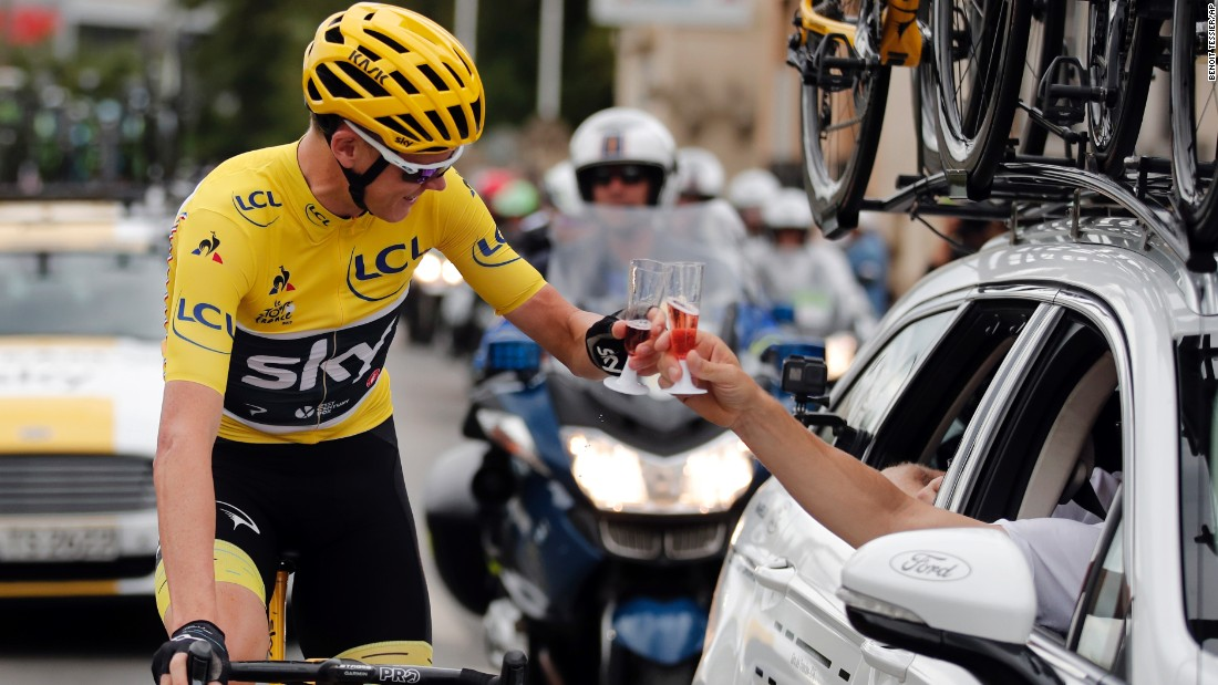 Froome toasts a member of his team during the last stage of the Tour de France race.
