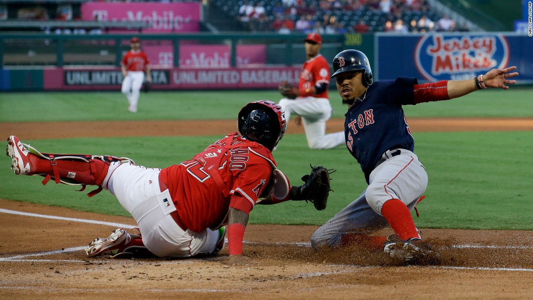 Boston's Mookie Betts, right, slides past Angels catcher Martin Maldonado during a Major League Baseball game in Anaheim, California, on Friday, July 21. It was the start of a five-run first inning for the Red Sox, who won 6-2.