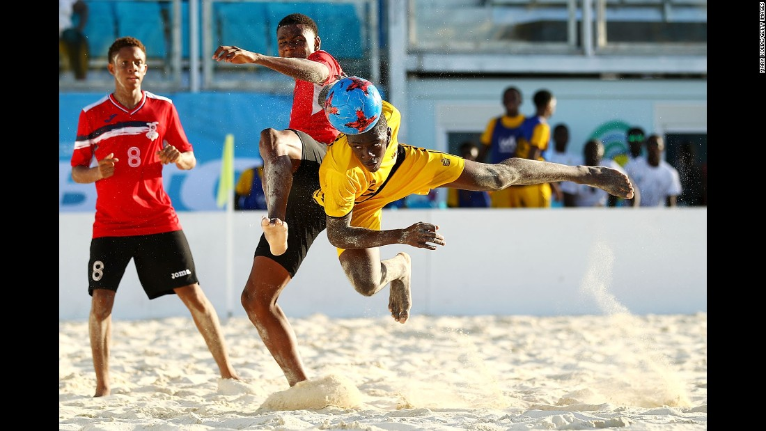Jajuan Williams, right, heads a ball for Antigua and Barbuda during a beach soccer match at the Youth Commonwealth Games on Wednesday, July 19. Trinidad and Tobago won after a penalty shootout.